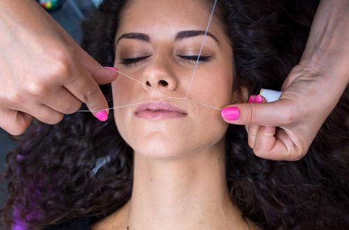 Attractive Brazilian woman getting her upper-lip threaded.