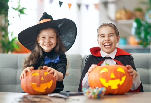 Happy Children on Halloween holding carved pumpkins.