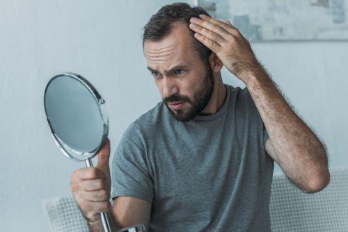 Man examining his hair loss in a mirror.