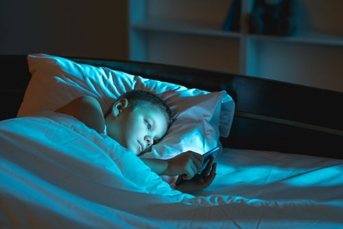 Young boy using his phone at night instead of sleeping.