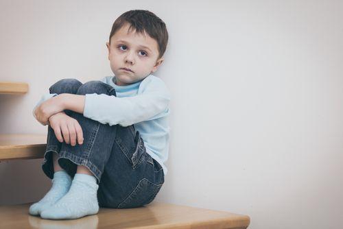Sad boy sitting on the stairs.
