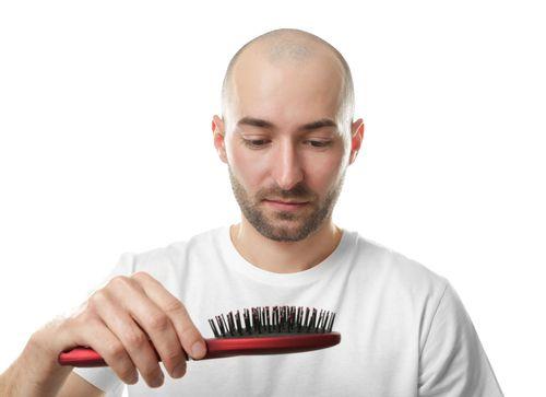 Sad bald man staring at a brush.