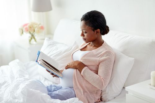 Pregnant African woman reading a book in bed.