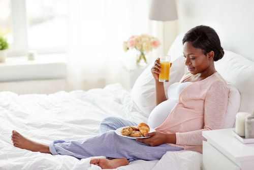 A pregnant African woman having cookies and orange juice in bed.