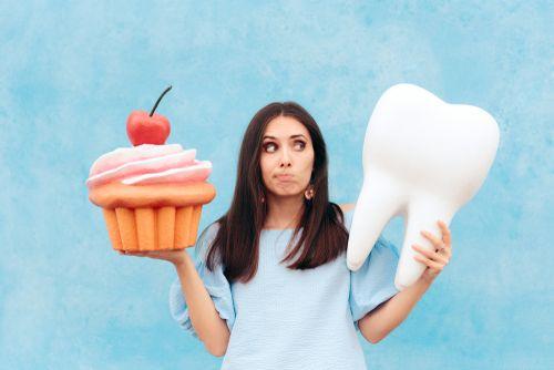 Woman choosing between cupcake and tooth.