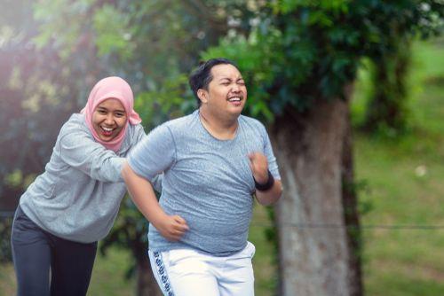 Hijabi woman running with her husband.