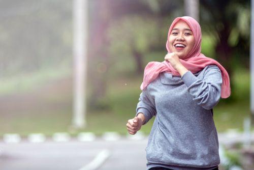 A hijabi woman running.