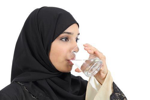 Woman in hijab drinking water.