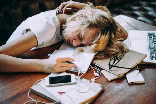 Girl sleeping whilst studying.
