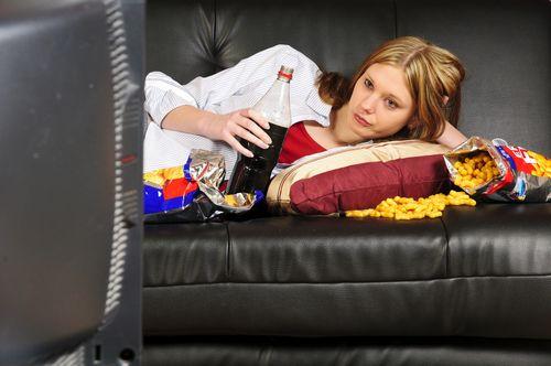 Woman watching netflix and eating junk food.