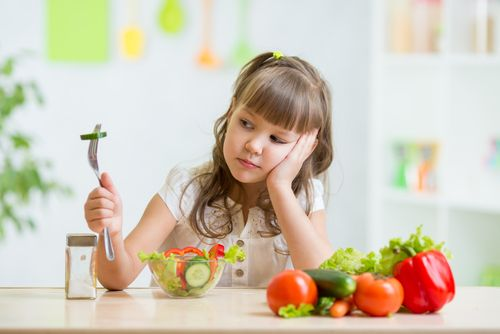Girl looking at her healthy food in disgust.