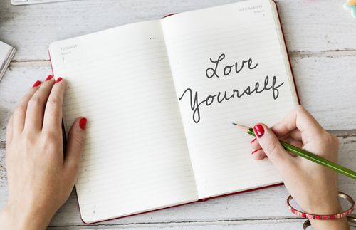 A woman writing 'love yourself' in her journal.