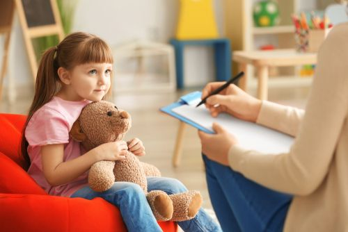A young girl with her teddy bear at the psychologist's clinic.