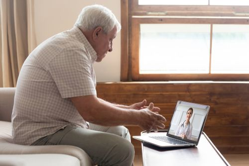 An elderly patient talking to his doctor from the ease of his home.